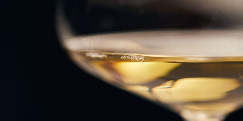 clear wine glass with yellow liquid